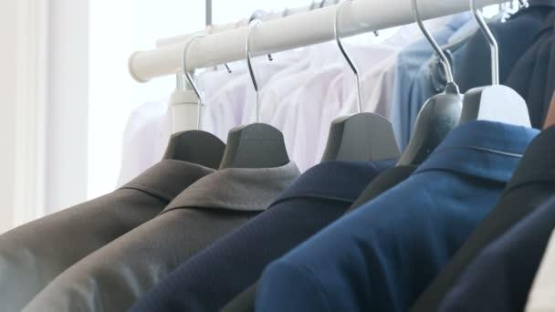 Košile, společenské obleky a trička v obchodě na závěs