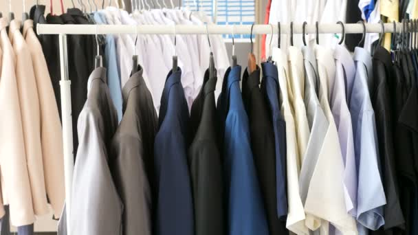 Different male business clothes, including suits and shirts on a hanger