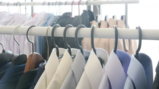 Different business clothes, including shirts and suits on a hanger in store