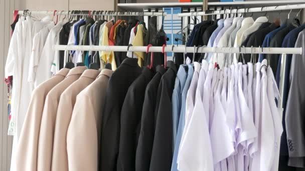 Kleiderbügel voller weiblicher und männlicher Kleidung