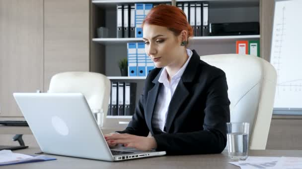 Smiling redhead businesswoman typing on the laptop