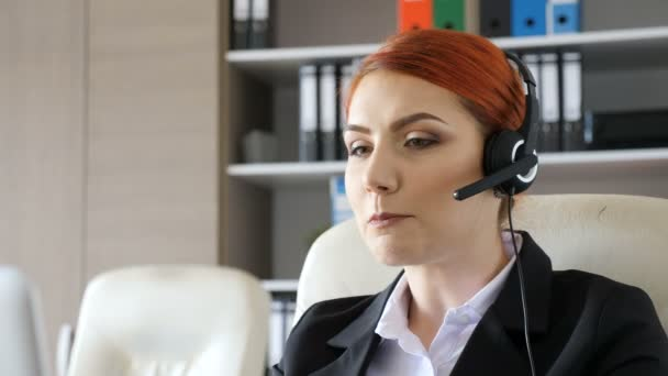 Hotline worker at her desk looking in the laptop and speaking through headset