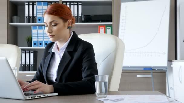 Podnikatelka u svého stolu v kanceláři psaní na notebooku