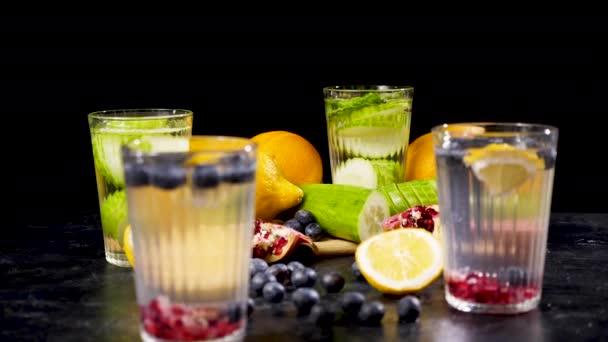 verschiedene Früchte und Beeren auf einem Holzbrett neben vier Gläsern Entgiftungswasser