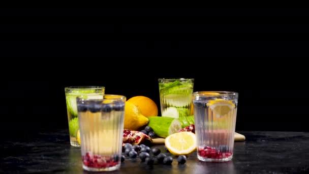 Különböző bio gyümölcsök mellett négy pohár vizet méregtelenítés