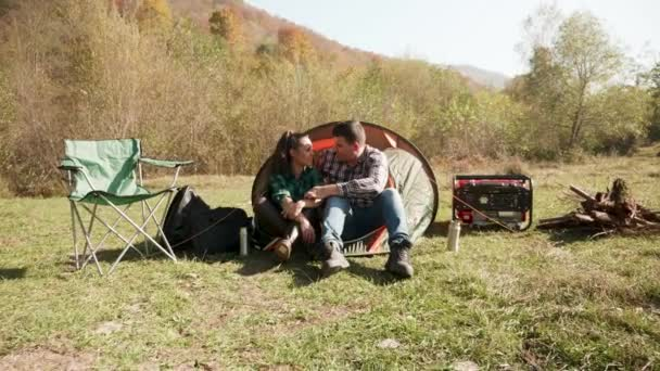 Beautiful young couple having a conversation in front of their camping tent