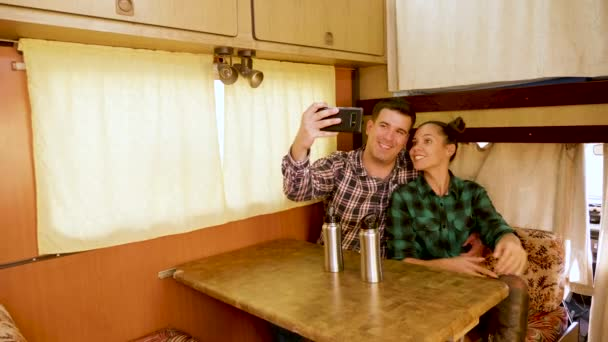 Beautiful young couple making a selfie inside of their retro camper van