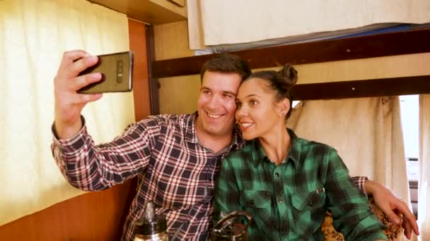 Cheerful young couple taking a selfie inside their vintage camper van