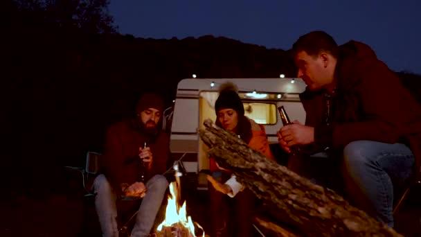 Běloch přítel těší pivo společně před jejich retro karavan