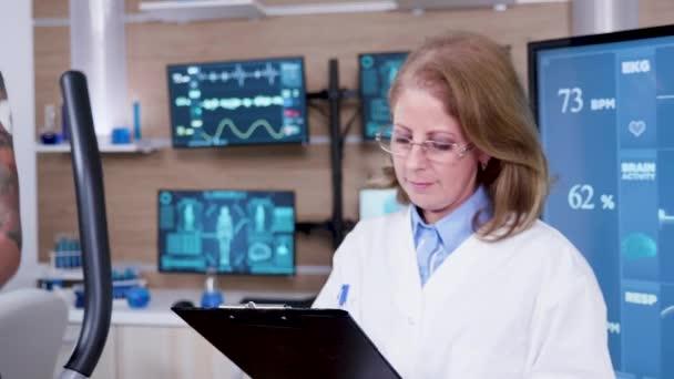 Medico femminile in scienze dello sport prendendo appunti sui suoi appunti