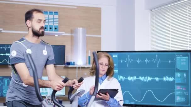 Medico femminile in scienze dello sport controllando le prestazioni di atleta maschile
