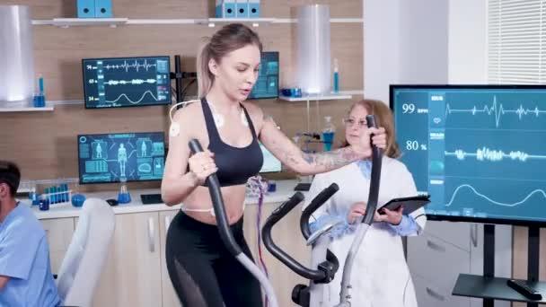 Medico femminile in scienze dello sport testando la frequenza cardiaca dellatleta femminile