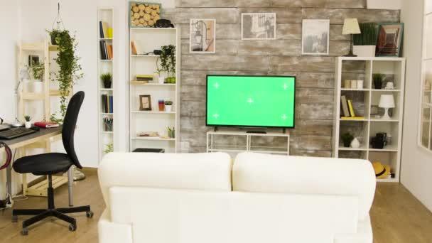 Zelená obrazovka TV v jasném a dobře osvětleném obývacím pokoji