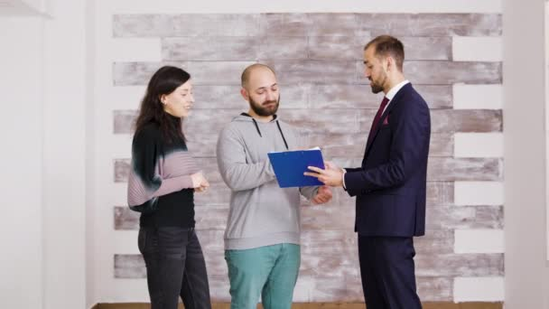 Immobilienmakler im Business-Anzug übergibt Schlüssel an junges Paar