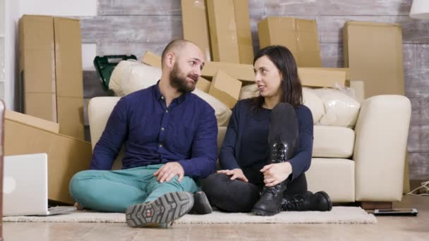 Beautiful young couple sitting on the floor of their new apartment