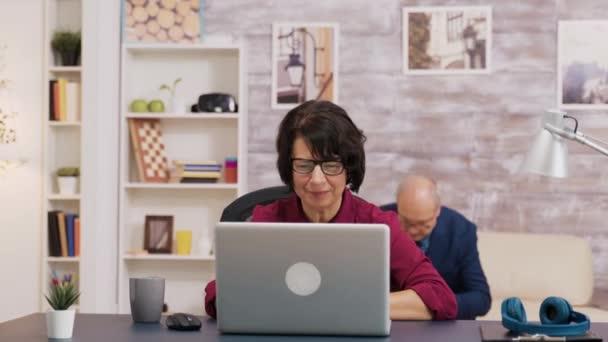 Aufgeregt alte Frau mit Laptop im Wohnzimmer