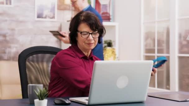 alte Frau genießt eine Tasse Kaffee, während sie am Laptop arbeitet