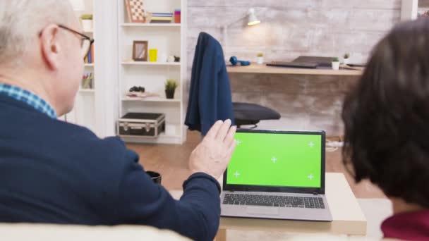 Rückansicht eines betagten Ehepaares, das am Laptop winkt