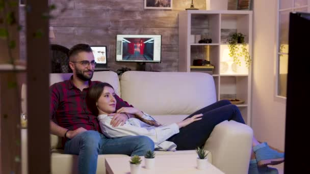 Charming couple lying on the couch watching a movie