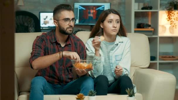 Koncentrált kaukázusi fiatal pár tévénézés közben