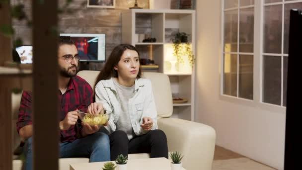 A barát takarja a barátnőjét, miközben horrorfilmet néz.