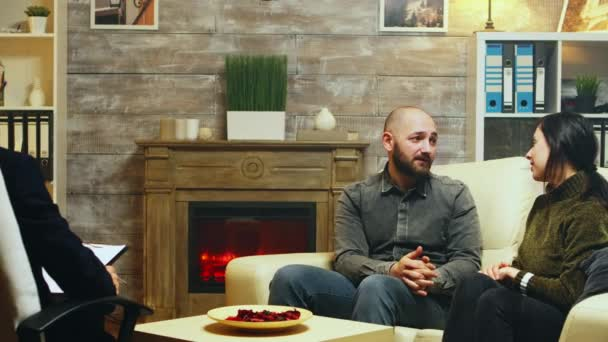 Young couple hug each other sitting on couch at therapy