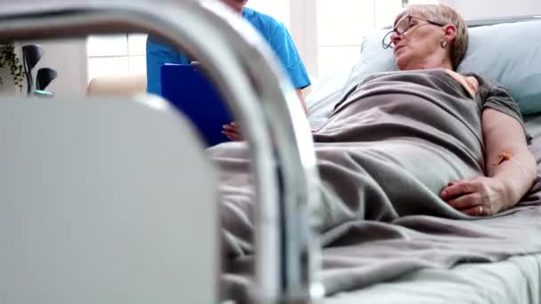 Female nurse taking notes on clipboard in nursing home