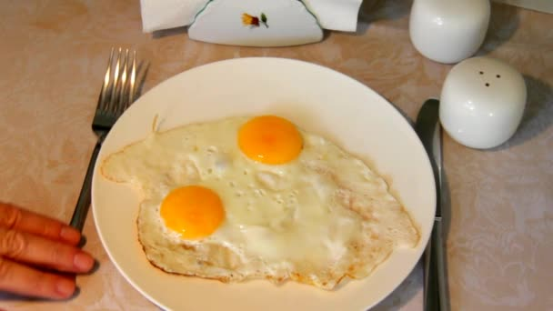 Szolgáló tojásrántotta egy tányérra, állva egy asztal terítő.
