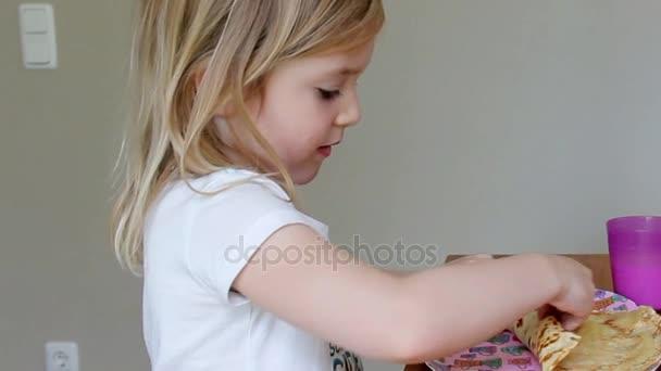 Děvčátko v bílých šatech jíst palačinky