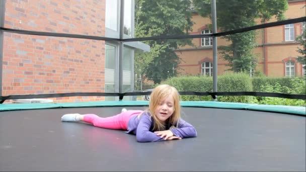 Kleines Mädchen springt auf Trampolin im Hof eines Privathauses