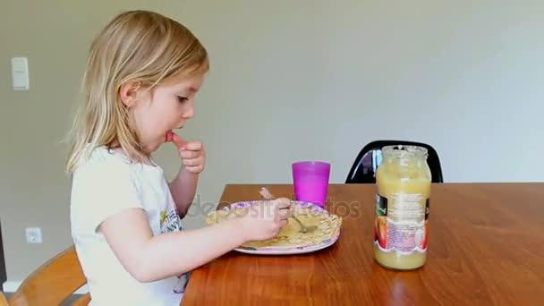 Malá holčička palačinky jídla a pití mléka doma
