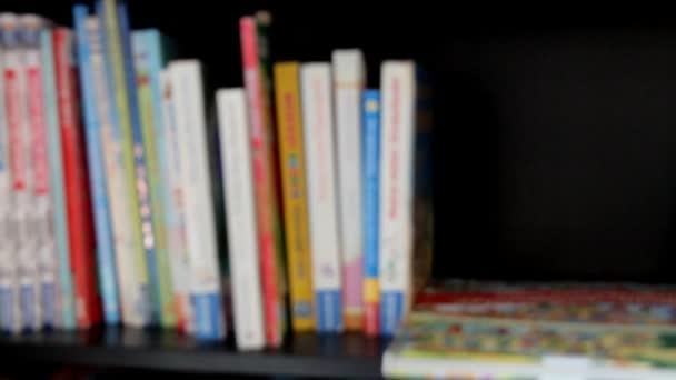 Rozmazaný pohled knih na dřevěné police.