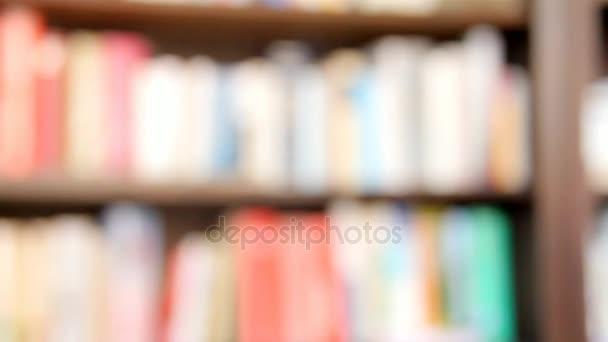 Homályos tekintettel a fából készült polcon a könyvek.