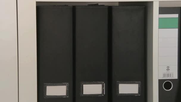 Makro zobrazení police s složky pro dokumenty. Kamera se pohybuje doprava
