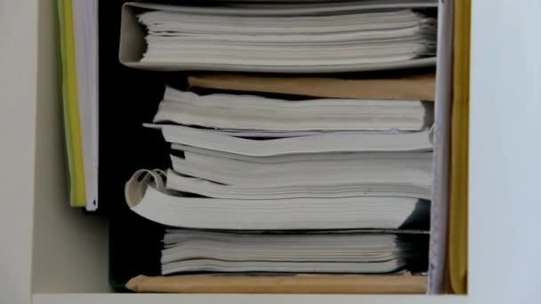Police s složky pro dokumenty. Kamera se pohybuje