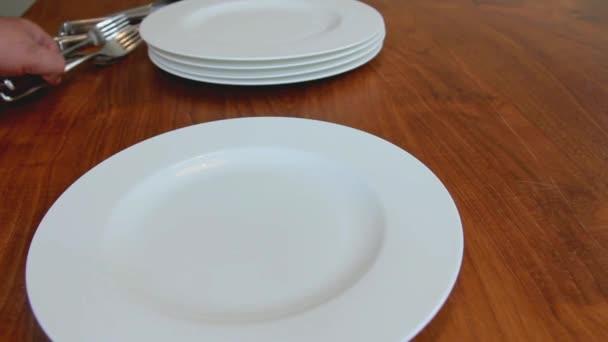 Male ruce uspořádáním porcelánové talíře a nádobí na hnědý dřevěný stůl