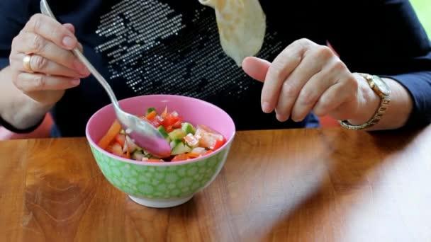 az idős nő eszik saláta ül egy barna fa asztal