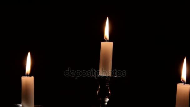 Hořící svíčky v stříbrný svícen na tmavém pozadí