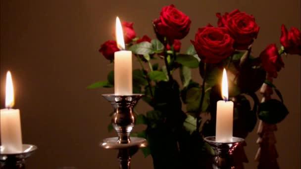 Hořící svíčky v stříbrný svícen na temné kytice červené růže v pozadí váza sklo