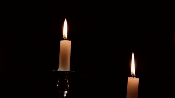 Hořící svíčky v stříbrný svícen na temné kytice Růže červené pozadí