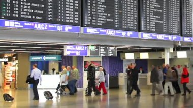 Passengers in One of the Halls of the Frankfurt International Airport With Flight Schedule Screens