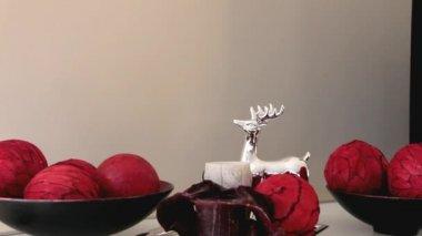 Vánoční dekorace Deer hračky a dekorativní květina stojící na bílé příborníku