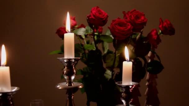 Zblízka pohled z hořící svíčky v stříbrný svícen na temné kytice z zvadlé červené růže v pozadí váza sklo