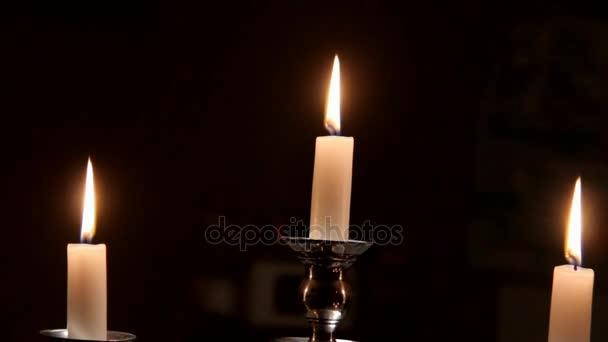 Zblízka pohled z hořící svíčky v stříbrný svícen na tmavém pozadí