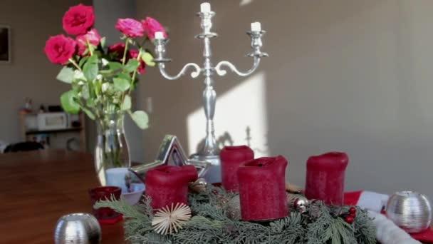 weihnachtliche Installation eines Rosenstraußes in einer Glasvase, eines silbernen Leuchters und roter Dekorkerzen auf einem Holztisch