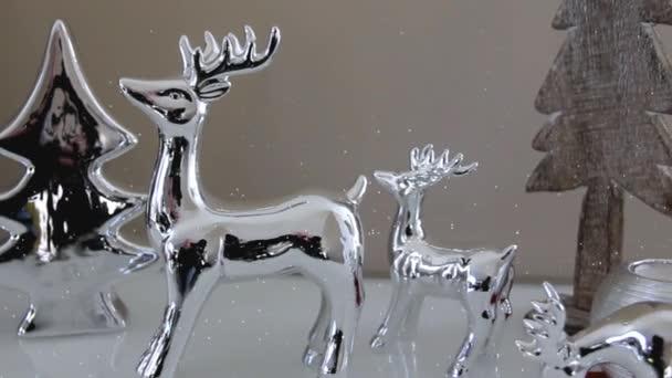 Vánoční dekorace hračky jeleny, vánoční stromky a dekorativní svíčka stojící na bílé příborníku