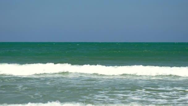 Hullámok ostromolják a lapos homokos strand lassítva