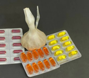 Fresh garlic , pills and vitamins in blister packs on dark background with copy space. Medical pharmacy concept. Selective focus. Blurred view