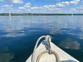 Fotografie Bootsfahrt auf einem schönen See bei blauem Himmel und angenehmer grüner Landschaft Hintergrund und schöne Reflexion auf der Wasseroberfläche. Segeln und Rudern sind eine beliebte Sportart