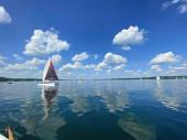 Fotografie Segelboot auf einem schönen See bei blauem Himmel und angenehmer grüner Landschaft Hintergrund und schöne Reflexion auf der Wasseroberfläche. Segeln ist eine beliebte Sportart und Aktivität